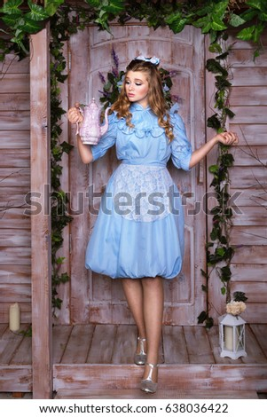 Alice holding the teapot standing at the door