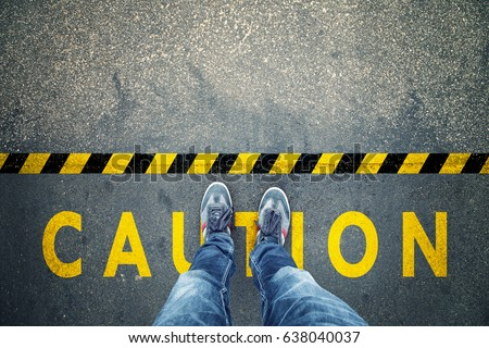 Top view of a man stands on industrial striped asphalt floor with warning yellow black caution pattern. Royalty-Free Stock Photo #638040037