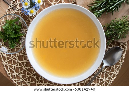 Bone broth made from chicken, served in a white plate, with chopped parsley, green herbs, and flowers in the background