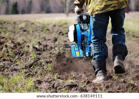 A man plows the land with a motoblock to sow plants. The machine like a mole loosens fertile soil. Agricultural machinery for cultivating soil in the garden town. Allows processing of large areas #638149111