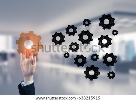 Hand of businesswoman touching glowing icon on screen and office at background #638215915