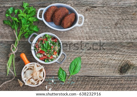 Table served with middle eastern traditional dishes. Bowl with falafel, vegetarian pita,  tabbouleh bulgur salad. Top view. Space for text. #638232916