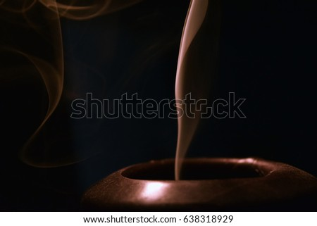 The smoke flow from an extinguished candle on a dark background #638318929