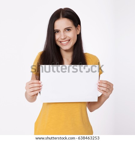 Your text here. Pretty young excited woman holding empty blank board. Studio portrait on white background. Mock up for design #638463253