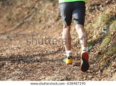 Muscular legs of the athlete runner from behind during the racing race in the mountain trail in winter #638487190