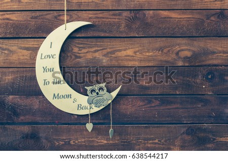I love you to the moon and back - wording on white moon with owl on a rustic wooden background with place for text. Happy St. Valentine's, Mother's Day. Love concept. Copy space. Toned image.