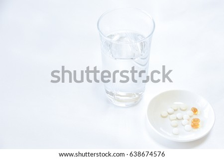 Medication concept. Tablets and a glass of water on white background #638674576