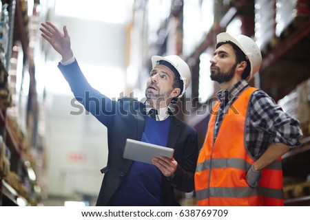 Businessman with touchpad pointing at upper shelf with goods while talking to worker #638769709