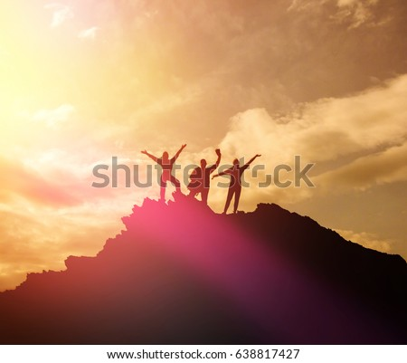 High academic performance, the silhouettes of three people, raise their hands up. A man on top of a mountain. Conceptual design. Against the dramatic sky with clouds at sunset. success #638817427