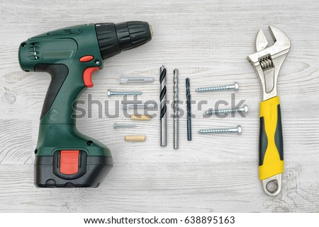 A cordless drill, a wrench, several drill bits, screw bolts and dowels on light wood background. Tools and equipment. Hardware store. Hand-made and renovation. #638895163