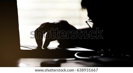 silhouette black and white of anonymous hacker typing on keyboard of laptop for remotely hacking and receiving personal information, Payment Security Concept  #638931667