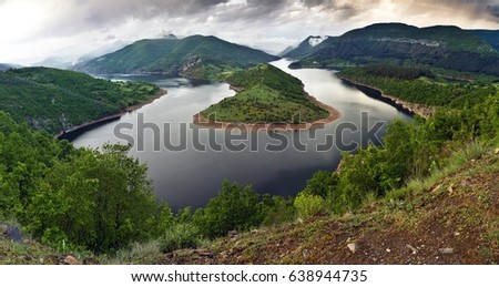 Arda's Meander against cloudy sky in summer day in Bulgaria. Reflecting smooth surface of turning river surrounded with green trees on hills