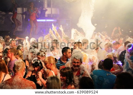 Koblevo, Ukraine July 14, 2011: crowd of people are full of happiness at foamy party in night club. Foam party in nightclub. #639089524