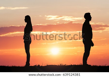 Couple Silhouette Standing Away From Each Other Against Dramatic Sky At Sunset #639124381