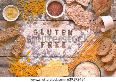 Gluten free flour and cereals millet, quinoa, corn bread, brown buckwheat, rice, bread and pasta with text gluten free in English language with spoon on wooden background,up view #639192484