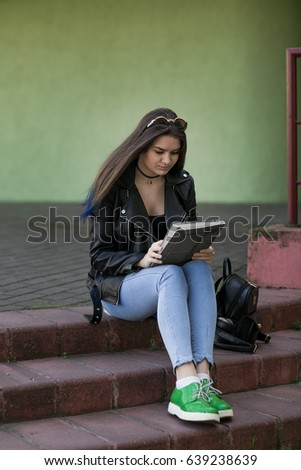 Girl using a digital tablet outdoors. #639238639