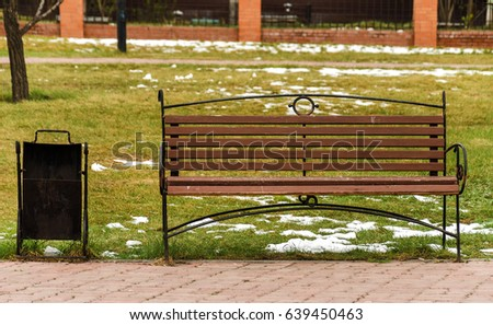 Forged bench and urn in the park #639450463