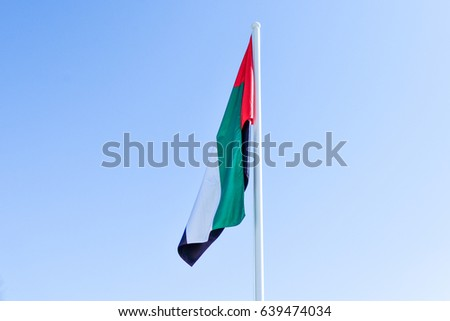 A United Arab Emirates flag flying against clean and tranquil sky. #639474034