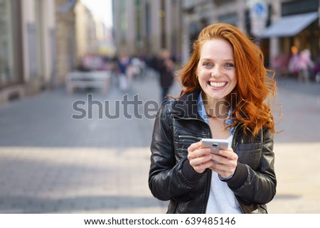 Happy friendly pretty young redhead woman using her mobile phone outdoors in an urban street as she stands grinning at the camera, with lateral copy space #639485146