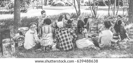 Group of friends making picnic with barbecue on city park outdoor - Young people eating bbq meal and drinking wine - Focus on bottom guys - Black and white editing - Vintage filter