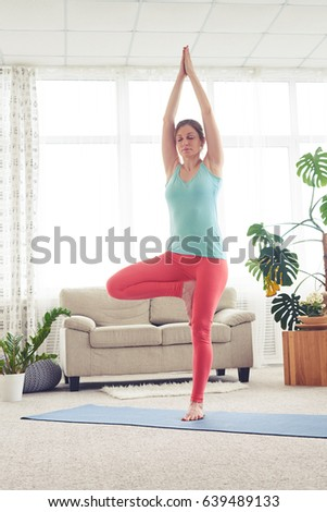 Vertical of nice girl in sportswear doing flamingo pose on yoga mat #639489133