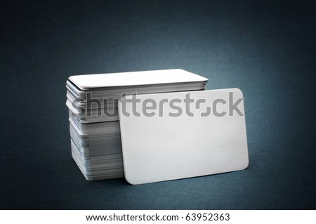 Business cards with rounded corners. The pile of blank business cards lays propped up another business card.