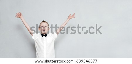 Happy cheerful kid with hands up against the grey wall
