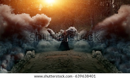 Young attractive Witch in black dress walking on the old bridge in heavy black smoke. Dark magic. Horror fairy tale. Royalty-Free Stock Photo #639638401