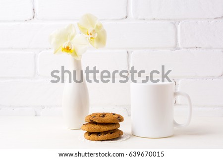 White coffee mug mockup with soft yellow orchid in vase and cookies.  Empty mug mock up for design promotion.   #639670015