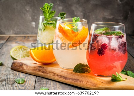 Selection of three kinds of gin tonic: with blackberries, with orange, with lime and mint leaves. In glasses on a rustic wooden background. Copy space  #639702199
