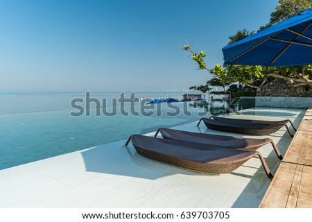 Modern Beach chairs poolside,Swimming pool at the ocean with beach chairs,Luxury sunbeds inthe water near swimming pool, Bangsaray beach Pattaya Thailand #639703705