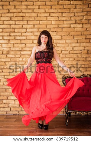 young beautiful brunette girl with flowing hair and blue eyes, dancing in a bright red dress with billowing hemline #639719512