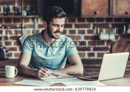 The young businessman using laptop, drinking coffee in the kitchen #639779854