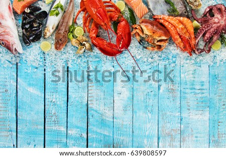 Whole lobster with seafood, crab, mussels, prawns, fish, salmon steak, mackerel and other shells served on crushed ice and wooden table #639808597
