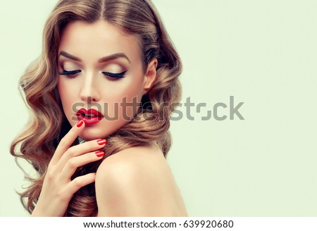 Beautiful  blonde model  girl  with long curly  hair . Hairstyle wavy curls . Red  lips and  nails manicure .    Fashion , beauty and make up portrait #639920680