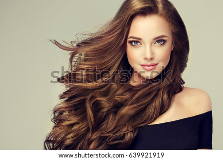 Brunette  girl with long  and   shiny wavy hair .  Beautiful  model with curly hairstyle . Royalty-Free Stock Photo #639921919