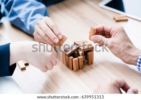 Businessmen are helping each other to complete the wooden stick model. Systematic work By clearly separating tasks, teamwork can be successful. And inspire new ideas. Close-up hands #639951313