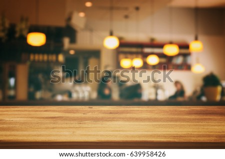 Image of wooden table in front of abstract blurred restaurant lights background. #639958426