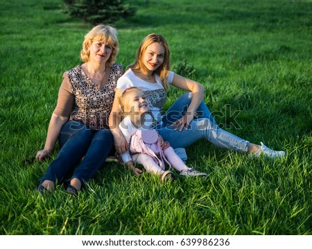 Happy family of Grandmother, Mother and daughter smiling at the park having picnic. They are sitting and resting on green lawn with grass #639986236
