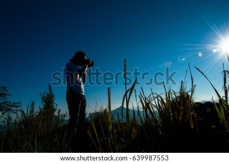A male photographer is taking a picture of the light from the morning sun. At the top of Doi Pha Tang. This is a tourist attraction of Thailand.