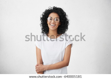 Positive human facial expressions and emotions. Isolated shot of attractive dark-skinned student girl in round eyewear looking and smiling broadly at camera during nice conversation with someone #640005181