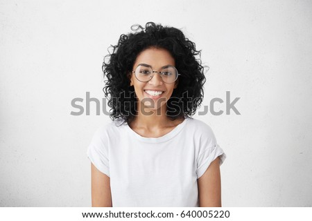 Indoor portrait of beautiful brunette young dark-skinned woman with shaggy hairstyle smiling cheerfully, showing her white teeth to camera while feeling happy and carefree on her first day-off #640005220