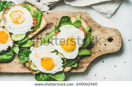 Healthy breakfast sandwiches. Bread toasts with fried eggs and fresh vegetables on rustic wooden board over grey marble background, top view. Clean eating, healthy, diet, weight loss food concept #640062460