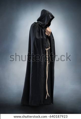 Silhouette of a praying monk, folded hands in prayer. Photo of monk at prayer. Full height. Concept for faith, spirituality and religion #640187923