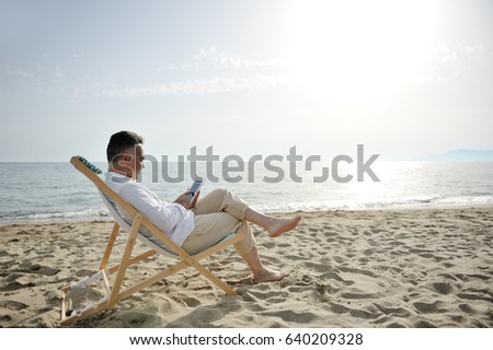 Man on holiday relaxing with tablet on the beach sitting on a deckchair #640209328