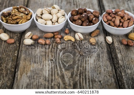 Nuts in a plate on a  wooden table. Different kinds of tasty and healthy nuts. #640211878