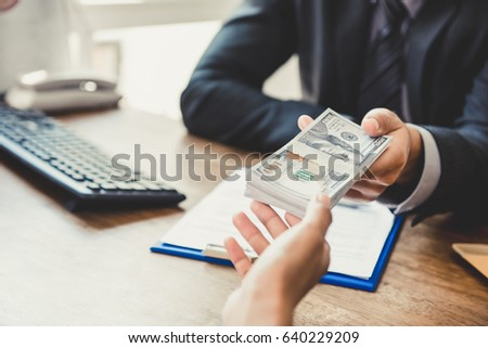 Businessman giving money to his partner while making contract - bribery and corruption concepts #640229209