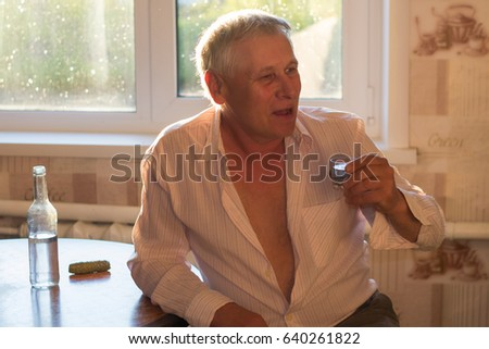 A gray-haired gray man is sitting at the kitchen table, on which stands a bottle of alcohol, a pickled cucumber, and holds a glass of vodka in his hand. Social problems: alcoholism #640261822
