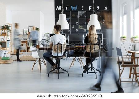 People in modern coworking space with blackboard calendar Royalty-Free Stock Photo #640286518