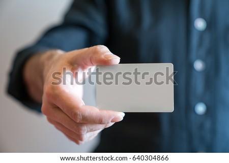Hand holding blank white credit card mockup front side view. Plastic bank-card design mock up  #640304866